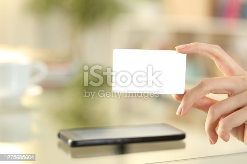 Woman hand showing a blank credit card at home