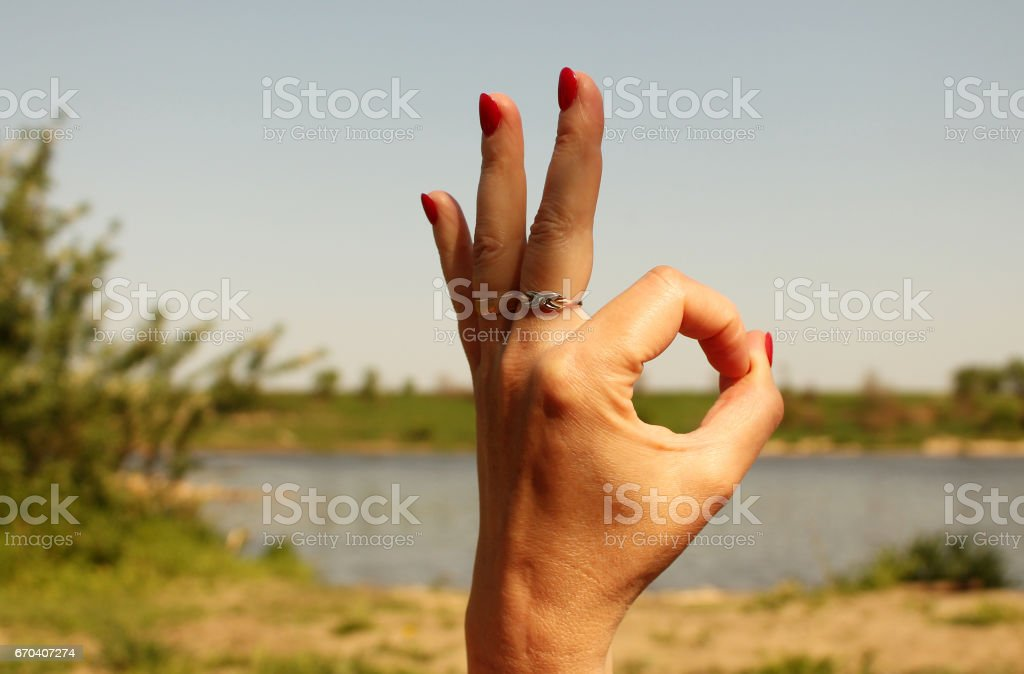 Woman hand  showing okay sign gesture, against backdrop of summer lake stock photo