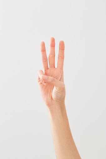 istock Woman hand showing peace three on white 1164273510