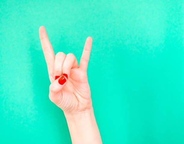 woman hand zeigt rock n roll hand-schilder isoliert auf türkisgrünen farbhintergrund. schild der hörner. wenn sie sich super cool fühlen, tun sie das rock n roll handzeichen - bester nagellack stock-fotos und bilder