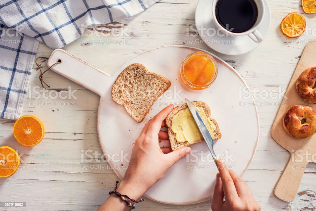 Woman hand spreading butter on sliced bread stock photo