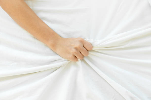Woman hand squeezing the sheet stock photo