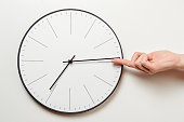 istock Woman hand stop time on round clock, female finger takes the minute arrow of the clock back, time management and deadline concept 1060502236