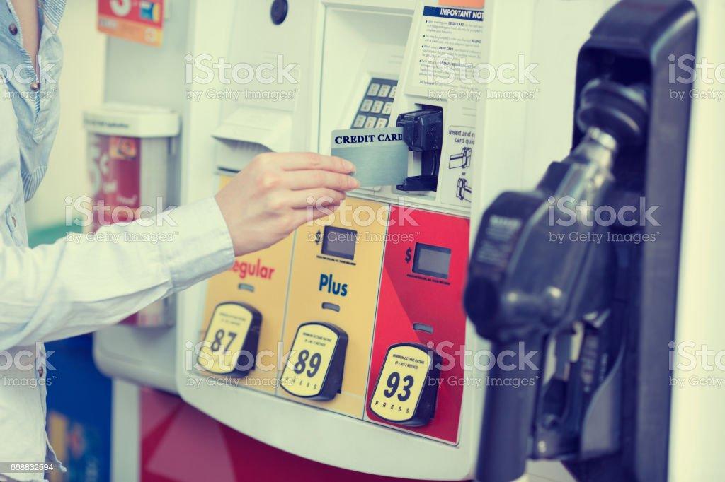 Woman hand swiping credit card at gas pump station. stock photo
