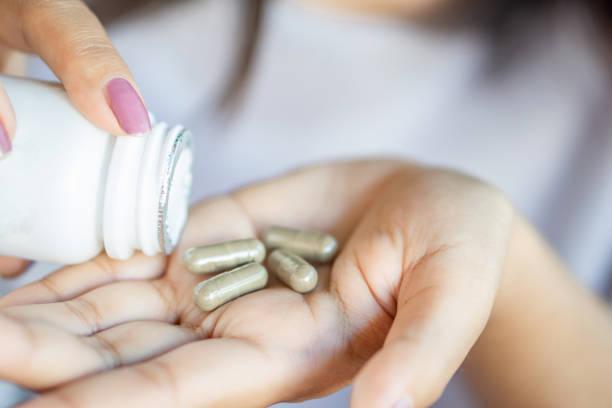 frau hand kräuter medizin tabletten - nahrungsergänzungsmittel stock-fotos und bilder