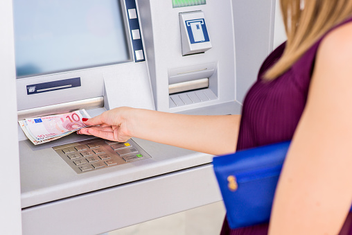 istock woman hand taking out euro banknotes from atm 593338442