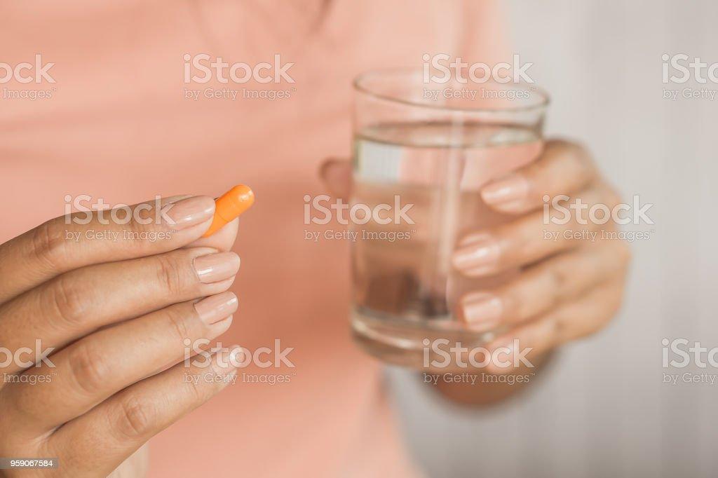 Frau Hand unter Pille und Glas Wasser in der hand – Foto