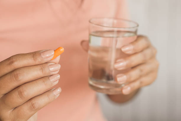 woman hand taking pill and glass of water in hand woman hand taking pill and glass of water in hand ,healthcare and medical woman taking pills stock pictures, royalty-free photos & images