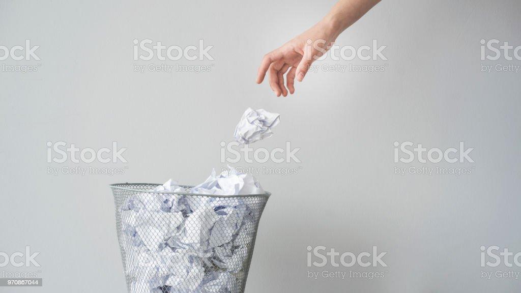 Kvinna hand kasta skrynklade papper i korg - Royaltyfri Avfallsbehållare Bildbanksbilder