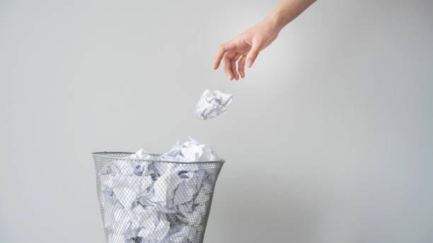 femme main jetant froissé papier dans le panier - jetée photos et images de collection