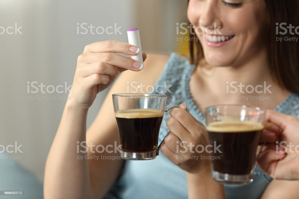 Woman hand throwing saccharine into a coffee cup stock photo