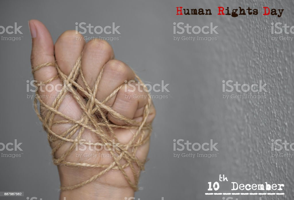 Woman hand tied with wire on dark background in low key. International human rights day concept. stock photo