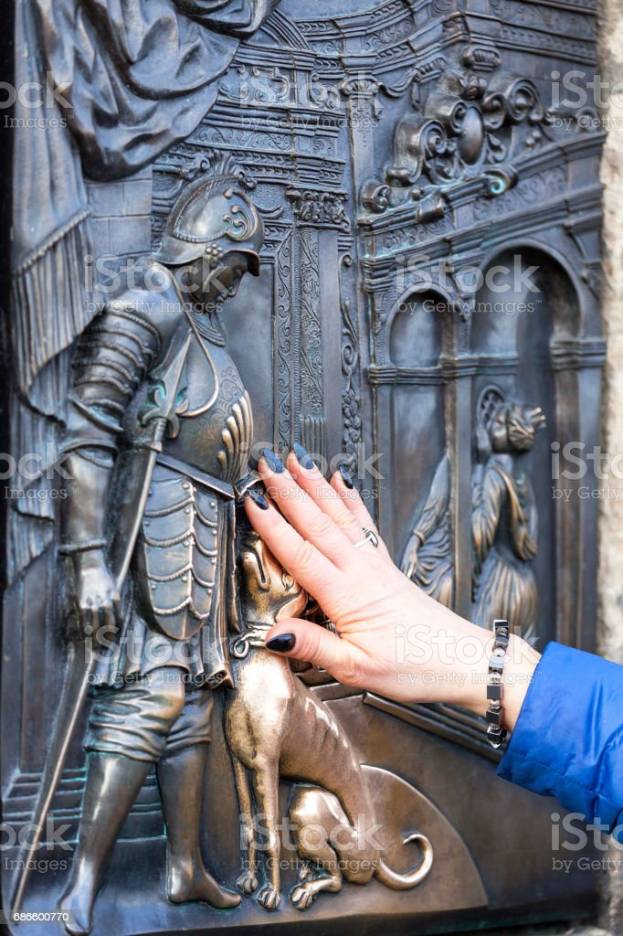Woman hand touching relief with John of Nepomuk for good luck, Charles Bridge, Prague, Czech Republic photo libre de droits