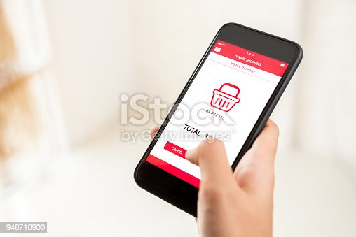 Woman hand touching button on smartphone screen, buying and making a payment digitally via application - internet online home shopping concept