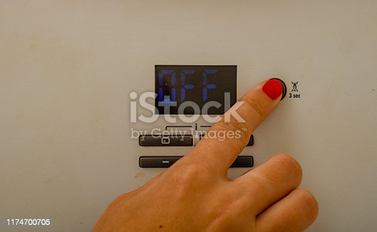 istock Woman hand try to turn off and on the central heating in the room. Female hands on the central heating control panel. Girl hand setting temperature to heating system. 1174700705