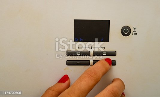 istock Woman hand try to turn off and on the central heating in the room. Female hands on the central heating control panel. Girl hand setting temperature to heating system. 1174700706