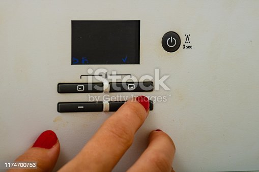 istock Woman hand try to turn off and on the central heating in the room. Female hands on the central heating control panel. Girl hand setting temperature to heating system. 1174700753