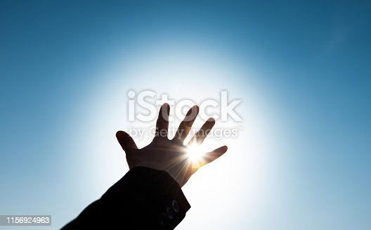 Woman hand trying to reach the sun.
