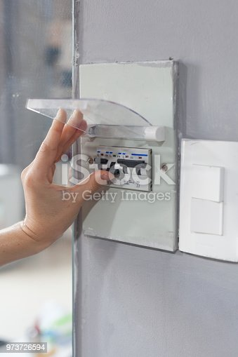 istock Woman hand  turning off fuse box in the house 973726594