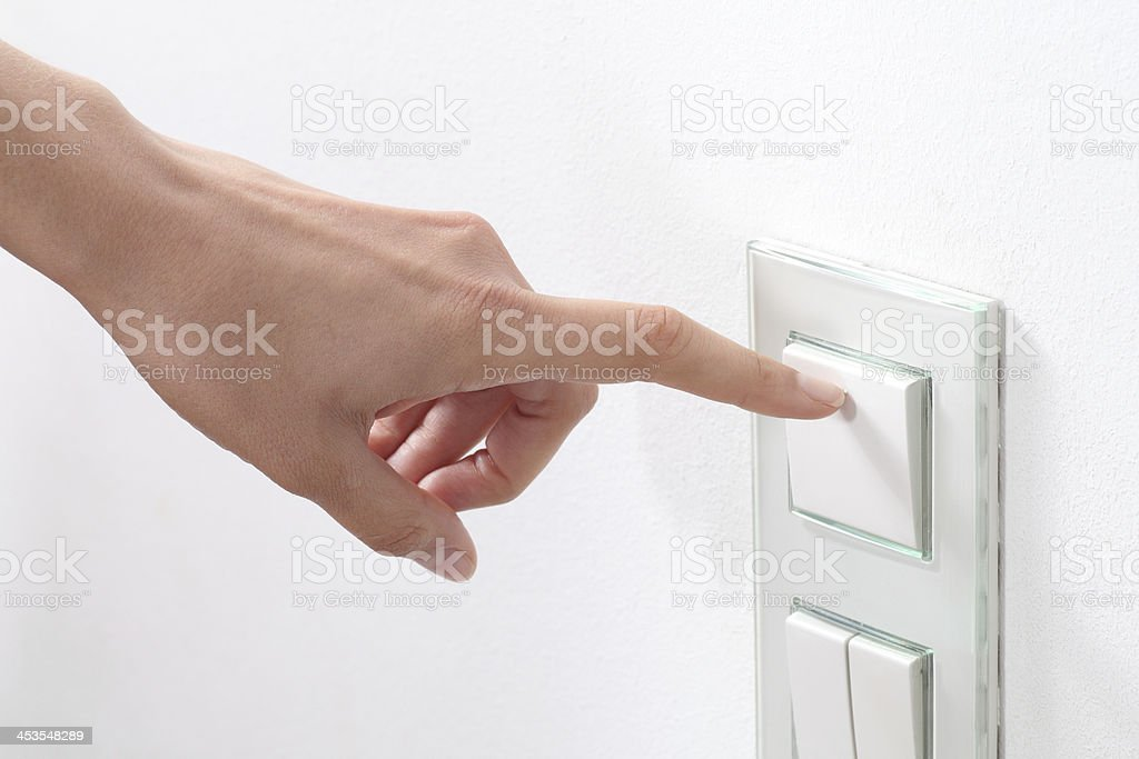 Woman hand turning operating a wall switch stock photo