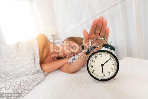 istock Woman hand turns off the alarm clock 1023159620