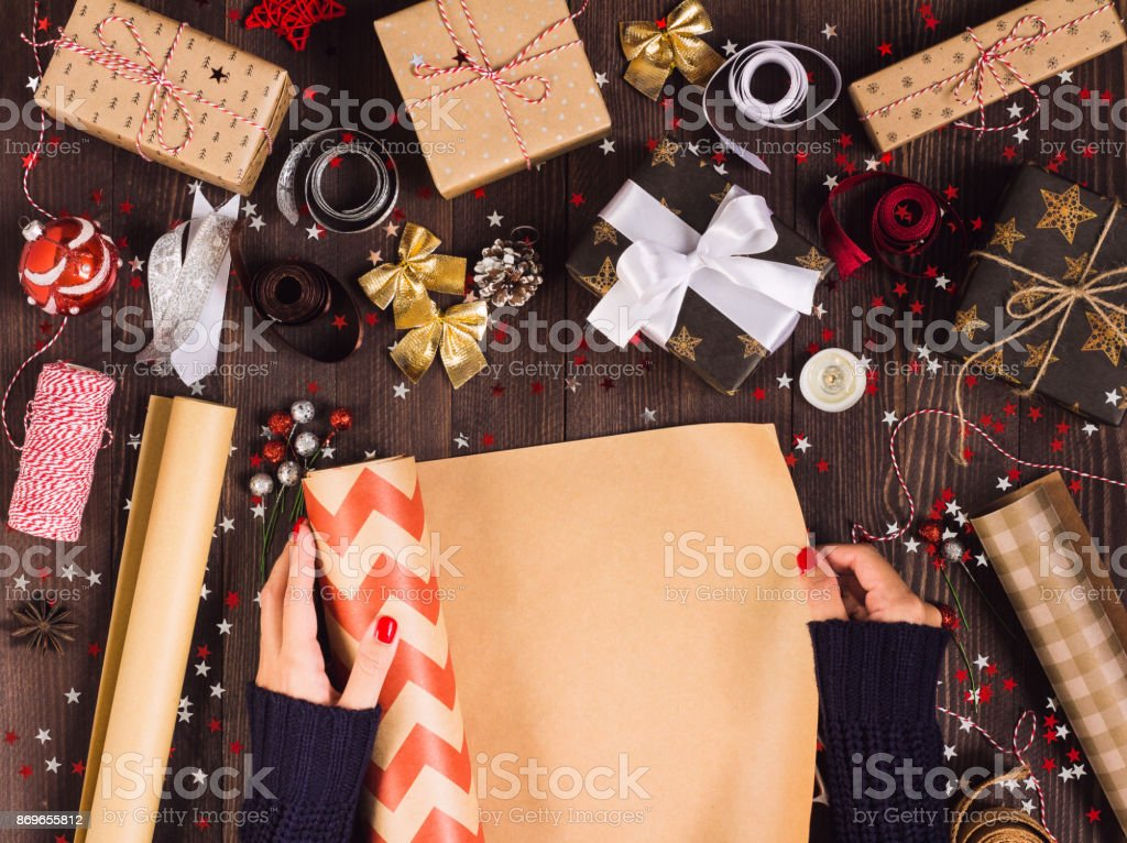 Woman hand unfolding roll of wrapping kraft paper for packing...