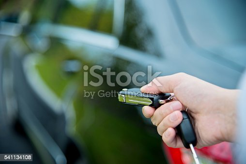 Woman unlocking a car by pressing on the remote control car alarm systems.