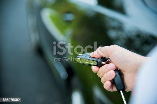 Woman unlocking a car by pressing on the remote control car alarm systems.
