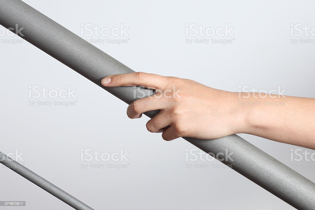 Woman hand using a railing to go upstairs stock photo