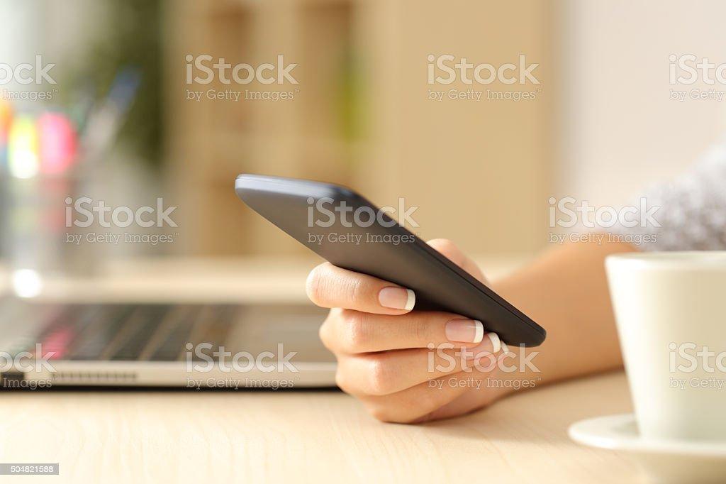 Mulher mão usando um telefone inteligente sobre uma escrivaninha foto royalty-free
