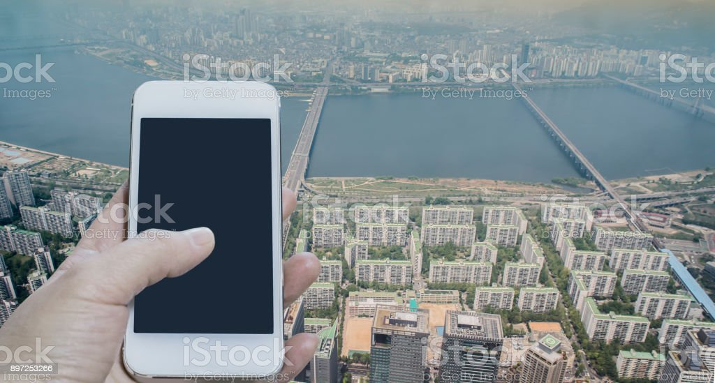 Woman hand using blank screen mobile smartphone over city scape and...