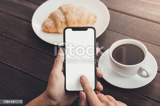 1084491176 istock photo Woman hand using blank smart phone during breakfast 1084491210