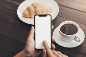 istock Woman hand using blank smart phone during breakfast 1084491210