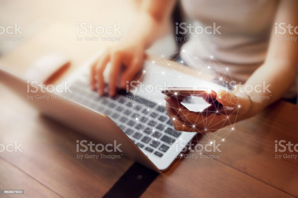 Woman hand using mobile phone and laptop, Worldwide connection technology interface. stock photo