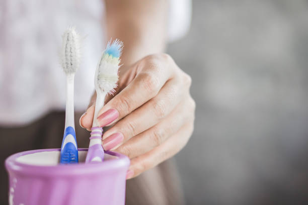 woman hand using old and destroy toothbrush closeup woman hand using old and destroy toothbrush closeup toothbrush stock pictures, royalty-free photos & images