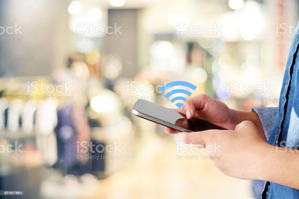 Main de femme en utilisant smart phone et icône de wifi sur le flou en magasin avec fond de bokeh, entreprise et concept technologique, marketing digital, - Photo