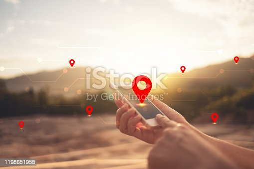 Woman hand using smart phone on top of mountain with navigator location point abstract background. Technology business and travel adventure concept. Vintage tone filter effect color style.