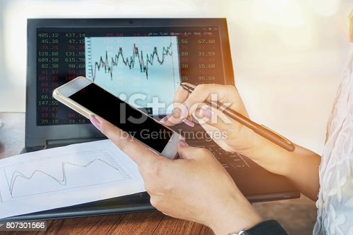 istock woman hand using smart phone while analyzing financial and stock graph 807301566