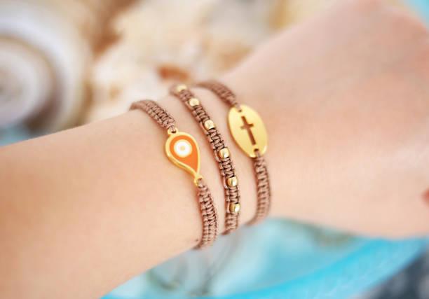 woman hand wearing stylish brown bracelets with evil eye and cross - macrame bracelets stock photo