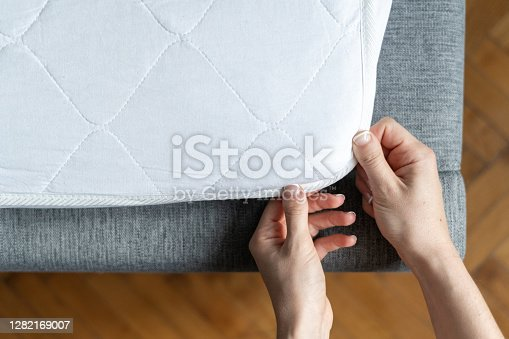 Top view of woman hand wearing topper at orthopedic mattress. Cropped view of female putting hypoallergenic surface with copy space background on sleeping bed