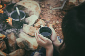 Close up woman hand with a coffee cup with grilling barbecue background in the campground at summer camp travel, Skewers of pork in camping, Summer Camp Travel one activity for relaxing.