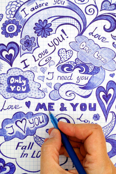 Woman hand with ballpoint pen draws love doodles messages on checkered paper. stock photo