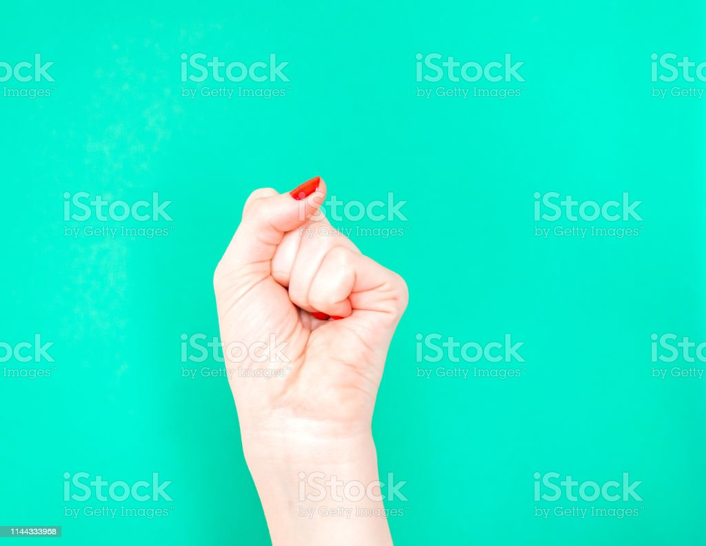 Woman Hand with clenched fist on isolated turquoise green color background. Woman Hand with clenched fist on isolated turquoise green color background. Adult Stock Photo