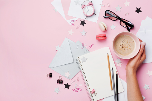 Woman hand with cup of coffee, macaron, office supply and empty notebook on pink pastel table top view. Fashion female blogger working desk.