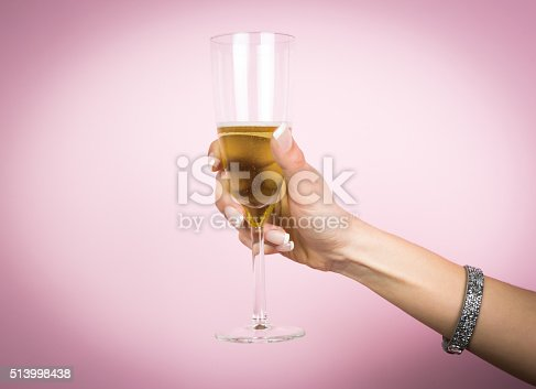 istock Woman hand with glass of champagne isolated on a pink 513998438