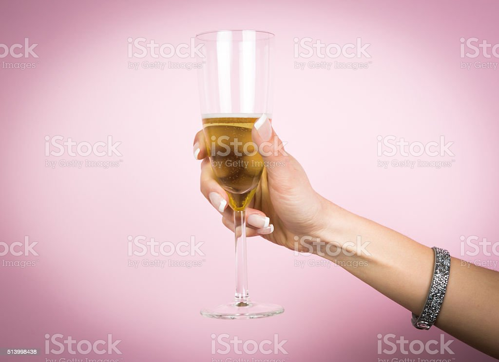 Woman hand with glass of champagne isolated on a pink stock photo