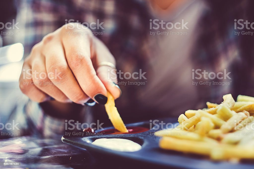 Woman hand with green nails tasting french fries with ketchup stock photo
