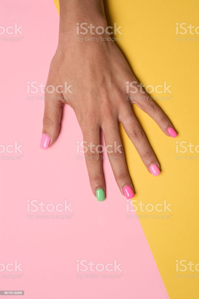 woman hand with her nails painted pink and green stock photo