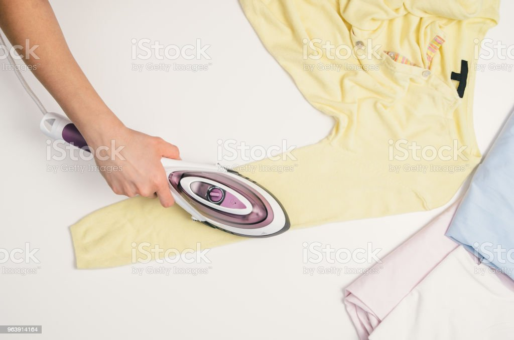 Woman hand with iron ironing clothes, top view - Royalty-free Above Stock Photo