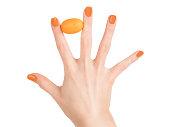 指の間の小さなオレンジ色の果物を保持しているオレンジ色の爪のポーランド語の女性手